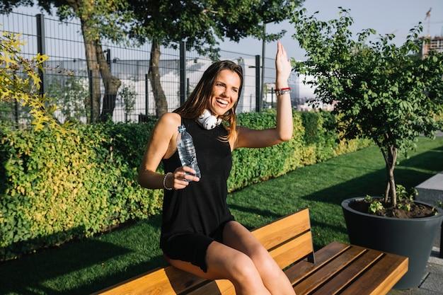 Glückliche frau mit der flasche wasser wellenartig bewegend ihre hand