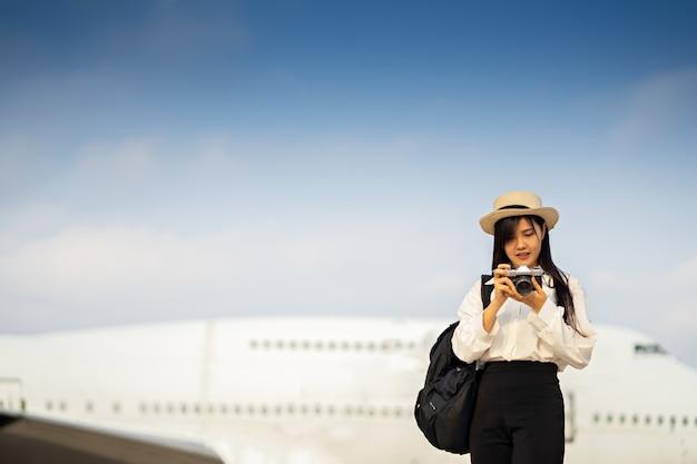 Glückliche frau mit der kamera, die auf reise mit dem flugzeug wartet.