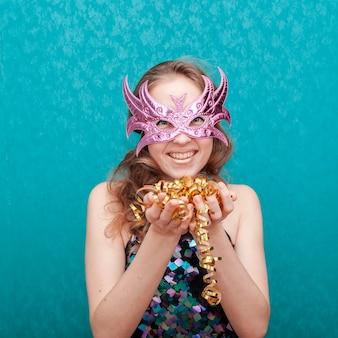 Glückliche frau mit der rosa maske, die bandkonfettis hält