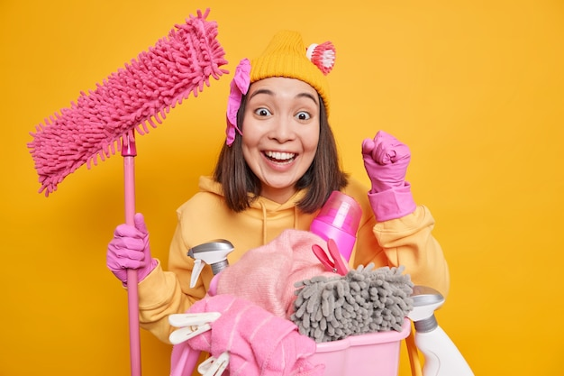 Glückliche frau mit dunklen haaren ballt fäuste und ist froh, wirksame reinigungsmittel und waschpulver zum reinigen von staub im raum zu verwenden, um wäsche zu waschen, hält mopp isoliert über gelber wand