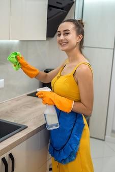 Glückliche frau mit eimer hatte ihre hausarbeit in der küche beendet