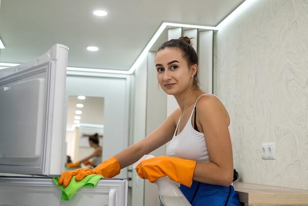 Glückliche frau mit eimer hatte ihre hausarbeit in der küche beendet Premium Fotos