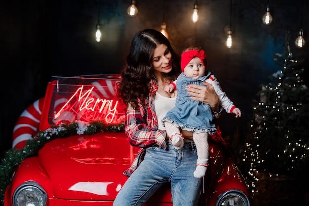Glückliche frau mit einem baby mit einer roten schleife auf dem kopf sitzen und haben spaß auf retro-auto mit weihnachtsdekoration