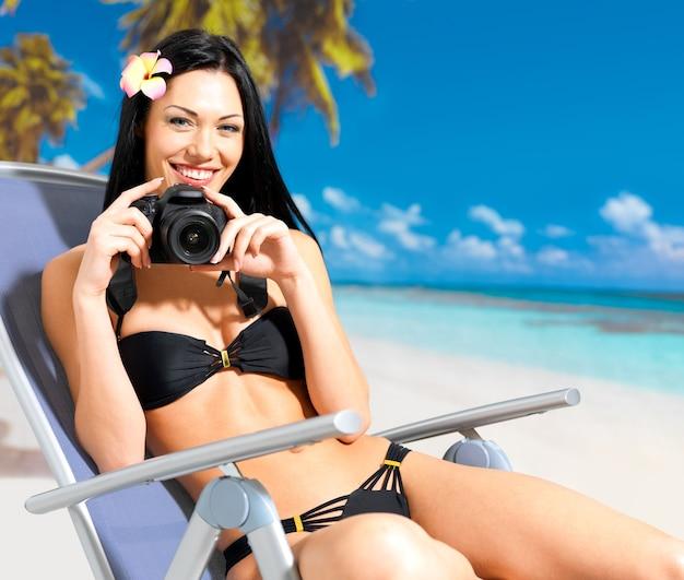 Glückliche frau mit einer digitalkamera, die fotos am strand macht