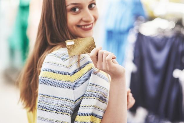 Glückliche frau mit einkaufstaschen und kreditkarte am speicher. der lieblingsberuf für alle frauen, lifestyle-konzept