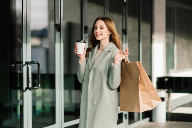 Glückliche frau mit einkaufstüten, die das einkaufen genießen. konsum, lifestyle-konzept