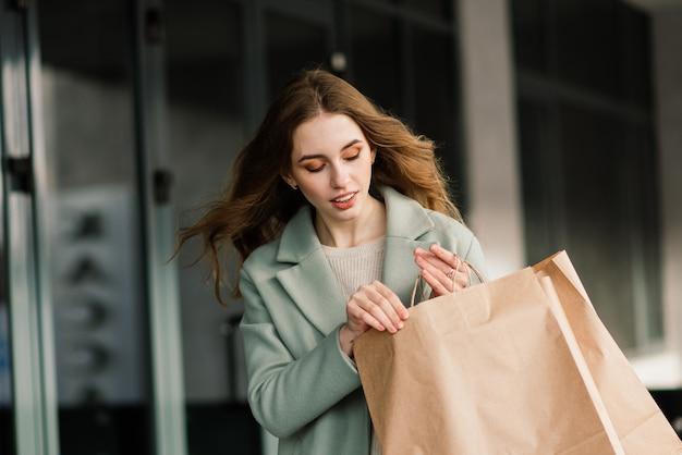 Glückliche frau mit einkaufstüten, die das einkaufen genießen. konsum, lifestyle-konzeption