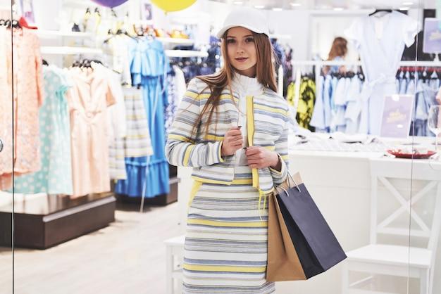 Glückliche frau mit einkaufstüten geht in den laden. der lieblingsberuf für alle frauen, lifestyle-konzept