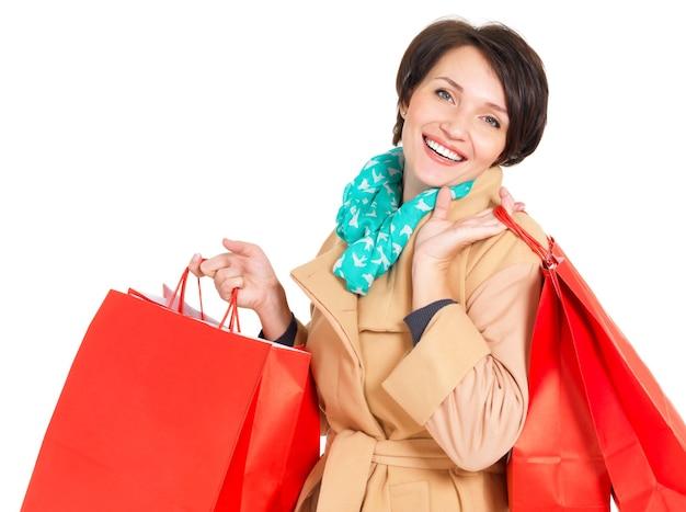 Glückliche frau mit einkaufstüten im beige herbstmantel mit grünem schal lokalisiert auf weiß