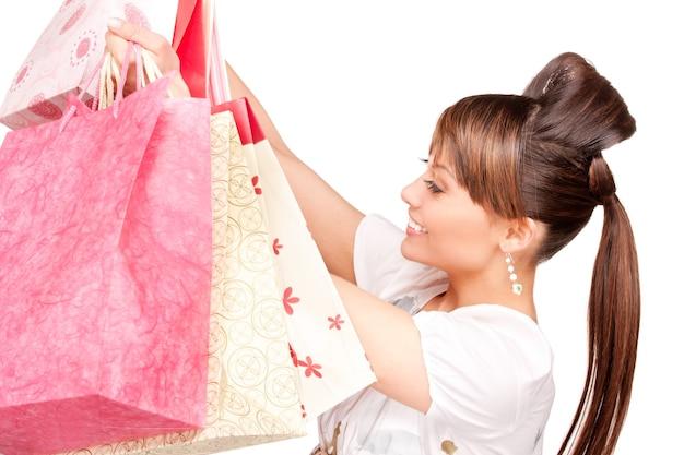 Glückliche frau mit einkaufstüten über weißer wand