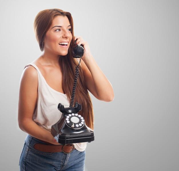 Glückliche frau mit festnetz-telefon und hörer