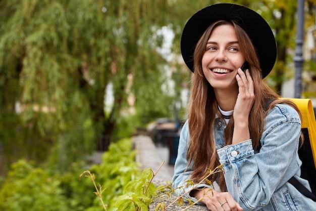Glückliche frau mit freudigem ausdruck, gekleidet in schwarzen stilvollen hut und jeansjacke, ruft auf handy zu freund an