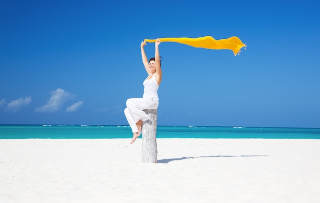 Glückliche frau mit gelbem sarong am strand