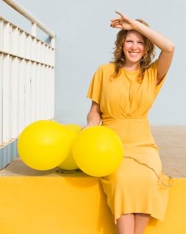 Glückliche frau mit gelben luftballons