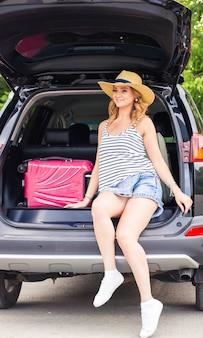 Glückliche frau mit gepäck im kofferraum. reisekonzept