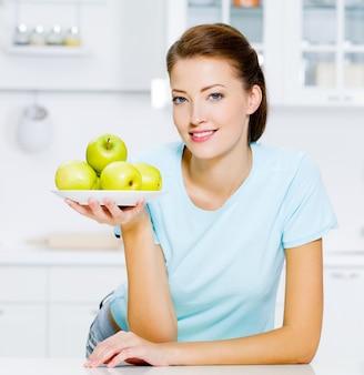 Glückliche frau mit grünen äpfeln auf einem teller in der küche