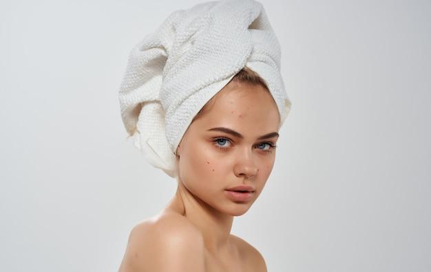 Glückliche frau mit handtuch auf ihrem kopf saubere hautkosmetologie nackte schultern.