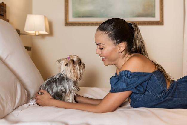 Glückliche frau mit hund auf weichem bett