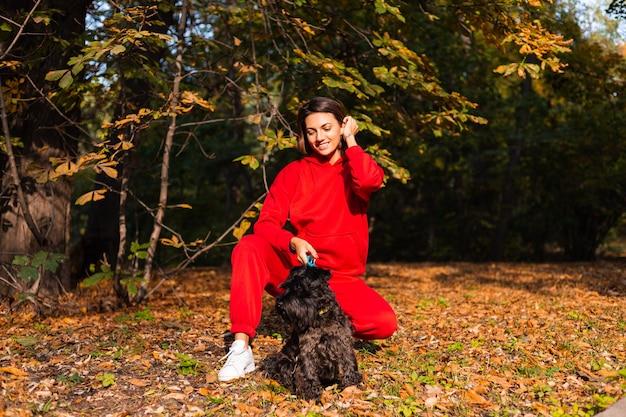 Glückliche frau mit hund im park mit herbstlichen blättern