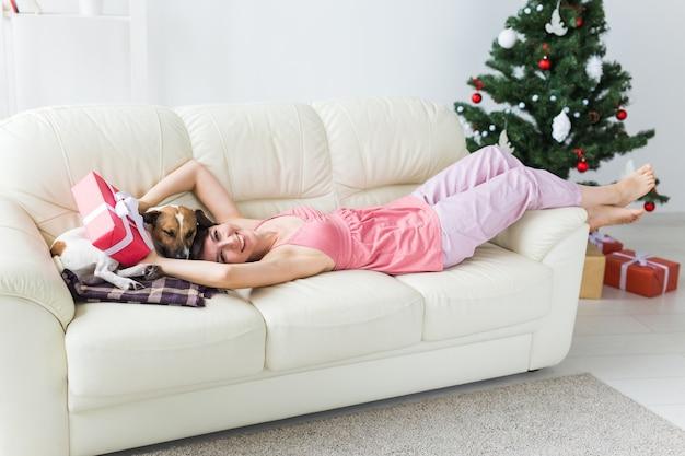Glückliche frau mit hund und weihnachtsbaum mit geschenken darunter