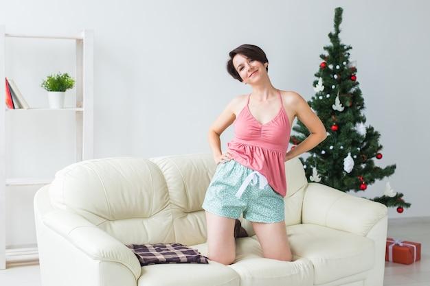 Glückliche frau mit hund. weihnachtsbaum mit geschenken darunter. dekoriertes wohnzimmer