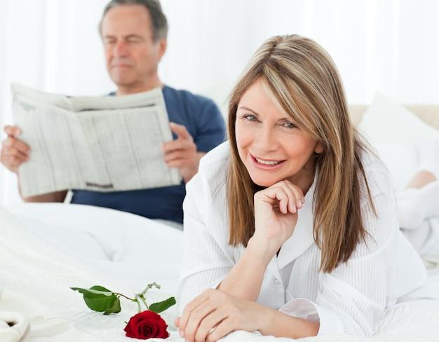 Glückliche frau mit ihr stieg, während ihr ehemann eine zeitung liest