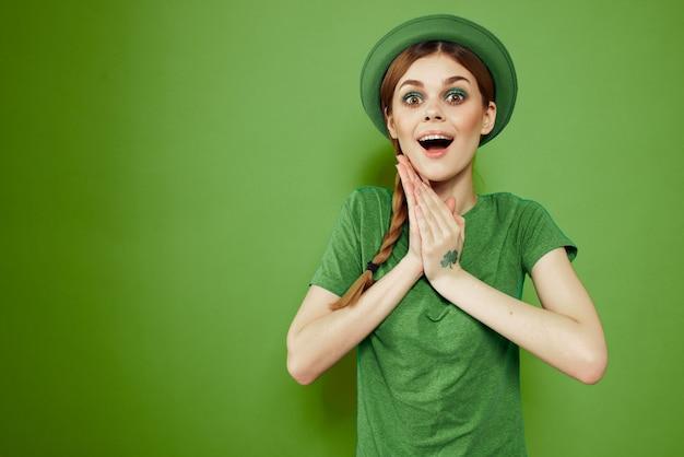 Glückliche frau mit kleeblatt am st. patrick's day in grünen kleidern und einem hut