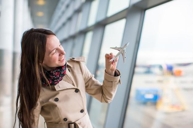 Glückliche frau mit kleinem flugzeugmodell innerhalb des flughafens