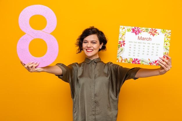 Glückliche frau mit kurzen haaren, die den papierkalender des monats märz und die nummer acht hält und die kamera anschaut und fröhlich den internationalen frauentag am 8. märz feiert, der über orangefarbenem hintergrund steht