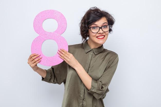 Glückliche frau mit kurzen haaren, die die nummer acht aus pappe hält und fröhlich lächelnd den internationalen frauentag am 8. märz feiert
