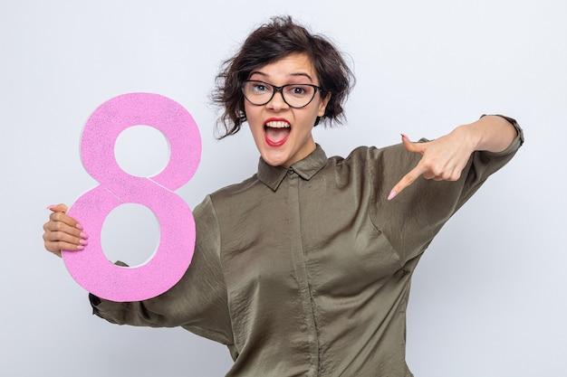 Glückliche frau mit kurzen haaren, die die nummer acht aus pappe hält und mit dem zeigefinger nach unten zeigt, fröhlich lächelnd den internationalen frauentag am 8. märz feiernd auf weißem hintergrund celebrating