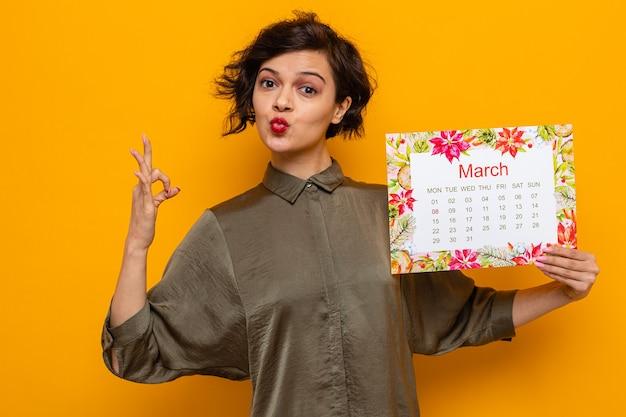 Glückliche frau mit kurzen haaren, die einen papierkalender des monats märz hält und ein ok-zeichen zeigt, das den internationalen frauentag am 8. märz feiert