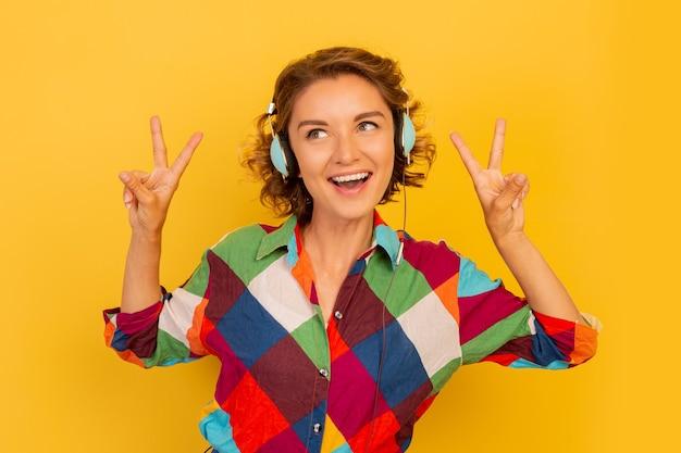 Glückliche frau mit kurzer frisur, die musik über kopfhörer hört und spaß über der gelben wand hat