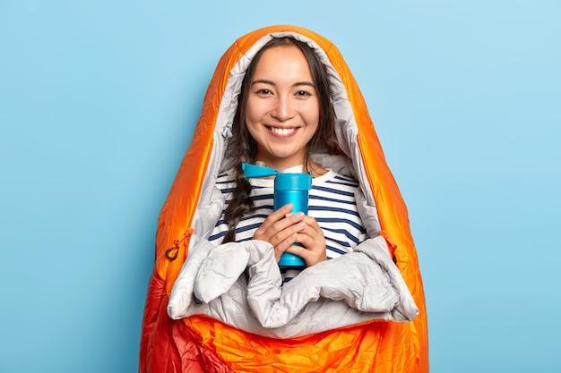 Glückliche frau mit langem zopf, steht in schlafsack gewickelt, hält thermoskanne mit heißem getränk, mag reisen und wandern