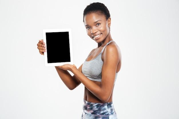 Glückliche frau mit leerem tablet-computerbildschirm isoliert auf einer weißen wand