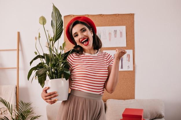 Glückliche frau mit roten lippen, die pflanze halten. modisches mädchen mit hellem hut, gestreiftem t-shirt und beigem rock freut sich in der wohnung.