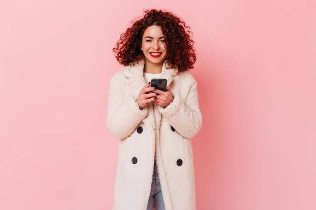Glückliche frau mit roten lippen und lockigem haar lächelt und hält telefon. porträt des freudigen mädchens im weißen öko-mantel und in den jeans auf rosa raum.