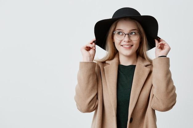 Glückliche frau mit scharfen augen und sanftem lächeln, retro-hut, brille und mantel tragend, seiten ihres hutes haltend. flitry blonde weibliche touristin mit erfreutem ausdruck isoliert.
