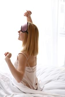 Glückliche frau mit schlafmaske, die morgens auf dem bett sitzt