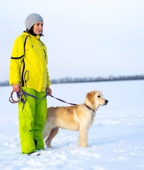 Glückliche frau mit schönem hundespaziergang im winter