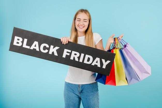 Glückliche frau mit schwarzem freitag-zeichen und bunten den einkaufenbeuteln getrennt über blau