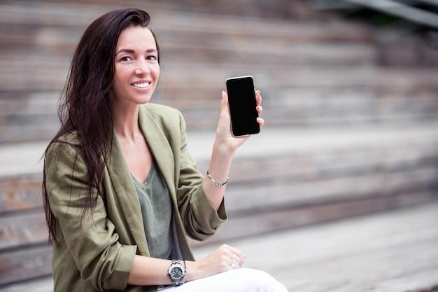 Glückliche frau mit smartphone draußen in der stadt
