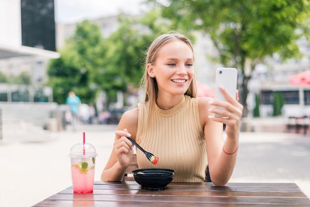 Glückliche frau mit smartphone macht selfie im straßencafé