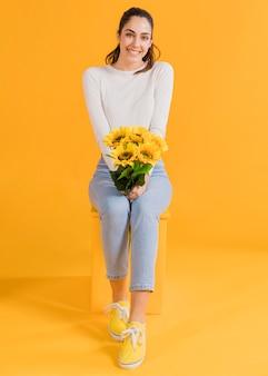 Glückliche frau mit sonnenblumenstrauß