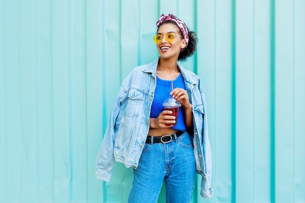 Glückliche frau mit stilvollen haaren, die im freien aufwerfen, kirschlimonade halten, jeansjacke und blauen wollpullover tragen.