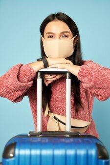 Glückliche frau mit tasche, die eine antivirus-gesichtsmaske trägt und sich auf einen koffer stützt