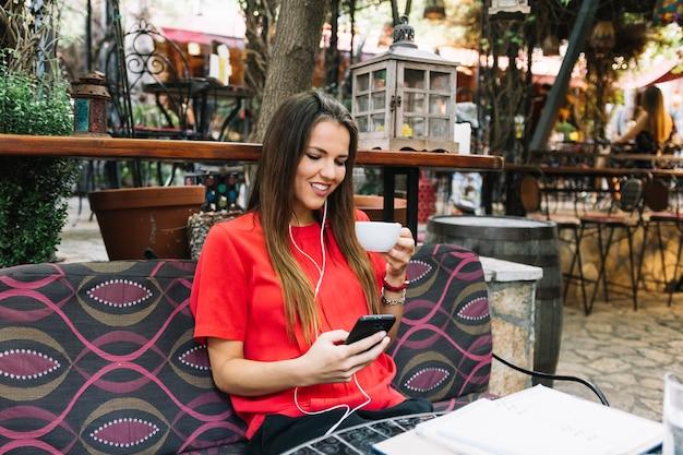 Glückliche frau mit tasse kaffee unter verwendung des mobiltelefons