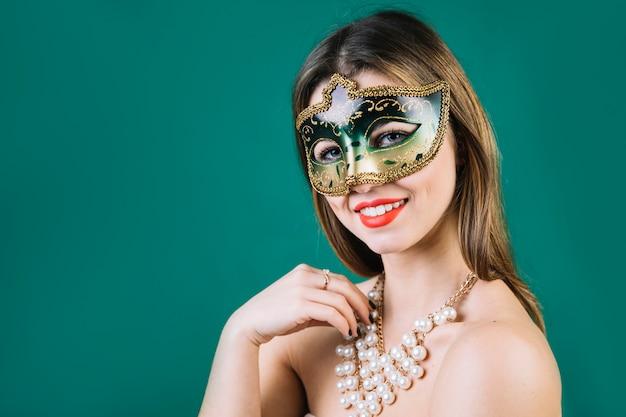 Glückliche frau mit tragender maskeradekarnevalsmaske der perlenhalskette auf grünem hintergrund