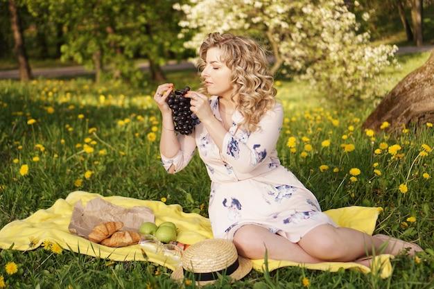Glückliche frau mit traube bei einem picknick im sommergarten