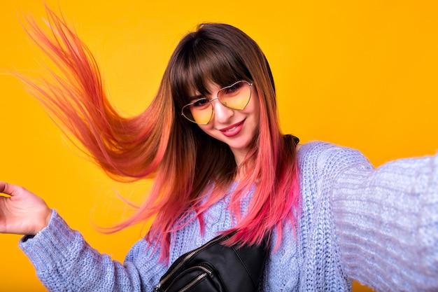 Glückliche frau mit ungewöhnlichen rosa haaren, die selfie an gelber wand, stilvollem kuscheligem pullover und herziger vintage-sonnenbrille machen.